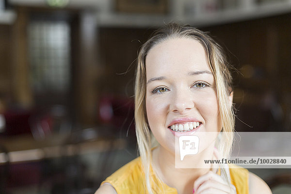Portrait of young woman smiling in cafe