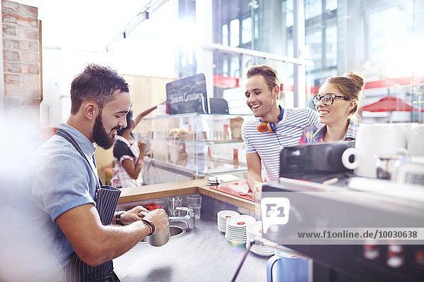 Kunden  die Barista bei der Kaffeezubereitung im Cafe zusehen.