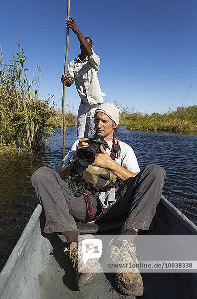 Wildbeobachtung  Fotosafari  Fotograf in einem traditionellen Mokoro Boot  Okavango Delta  Moremi Wildreservat  Botswana  Afrika