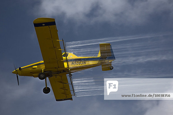 Crop duster airplane applies pesticides to a field in the Mississippi Delta  Tunica  Mississippi  USA