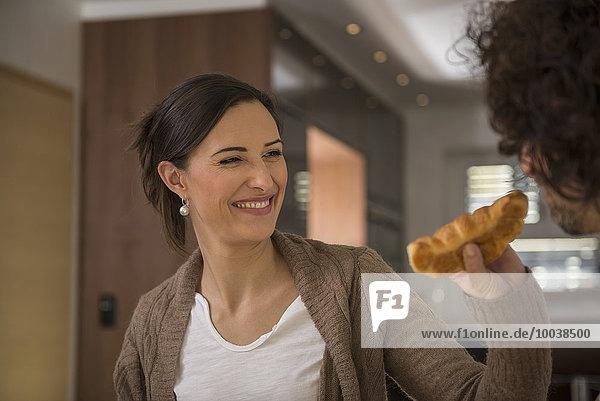 Woman's hand feeding a croissant to her husband  Munich  Bavaria  Germany