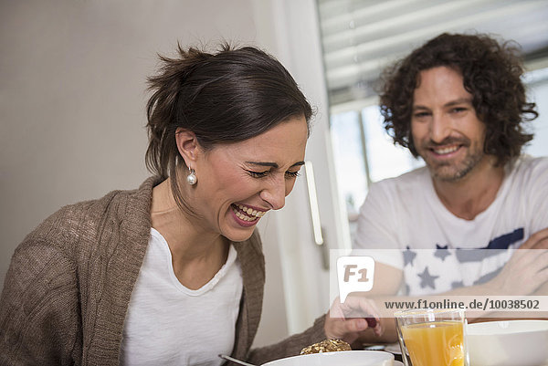 Mid adult couple smiling at breakfast table  Munich  Bavaria  Germany