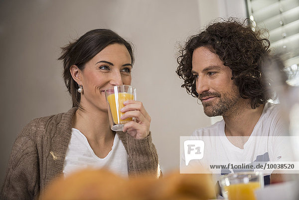 Mid adult woman drinking juice while her husband looking at her  Munich  Bavaria  Germany