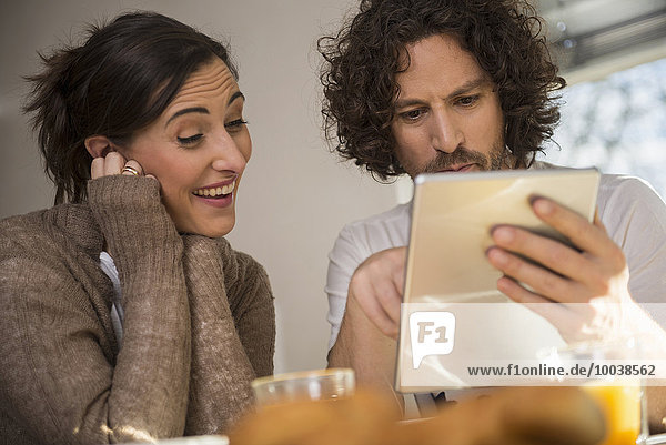 Mid adult couple using a digital tablet  Munich  Bavaria  Germany