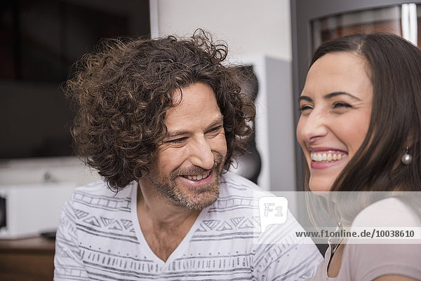 Close-up of mid adult couple smiling in living room  Munich  Bavaria  Germany