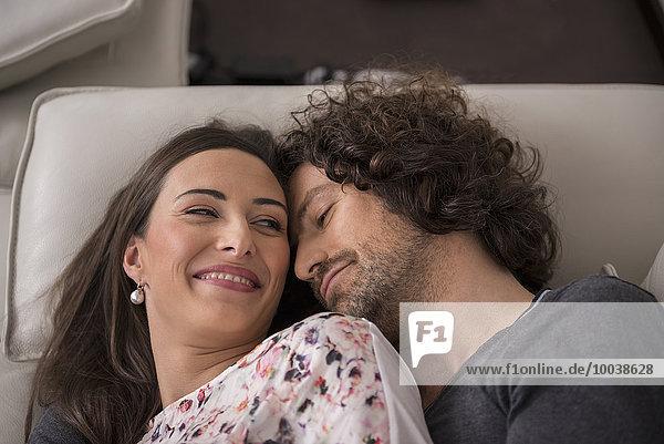 Mid adult couple sleeping on sofa  Munich  Bavaria  Germany