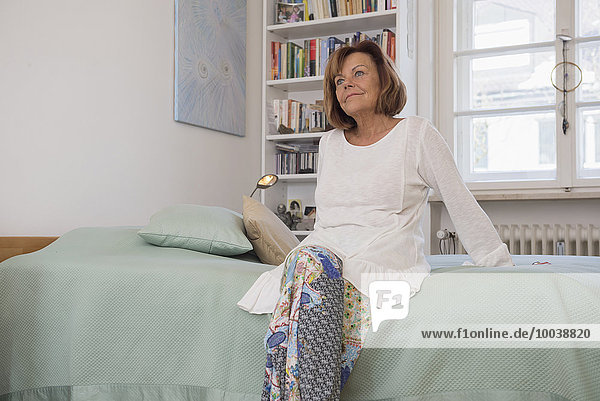 Senior woman sitting on bed and dreaming  Munich  Bavaria  Germany
