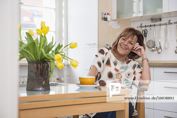 Happy senior woman having tea at a dining table in kitchen  Munich  Bavaria  Germany