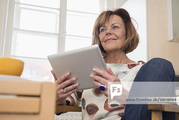 Low angle view of a senior woman sitting on chair and using a digital tablet  Munich  Bavaria  Germany