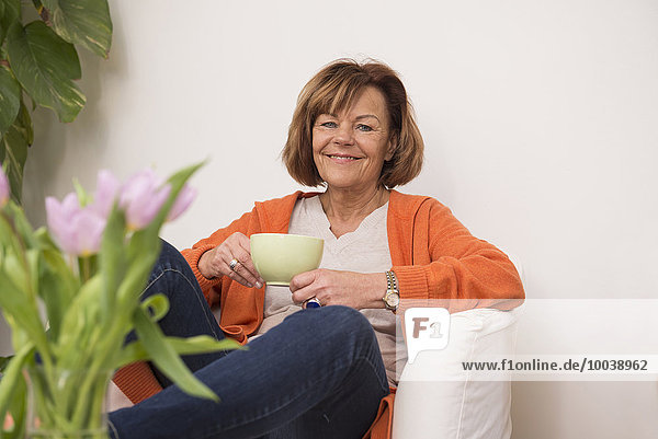 Happy senior woman sitting on sofa and having cup of tea at home  Munich  Bavaria  Germany