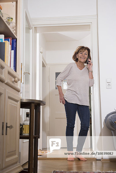 Senior woman talking on mobile phone at doorway  Munich  Bavaria  Germany