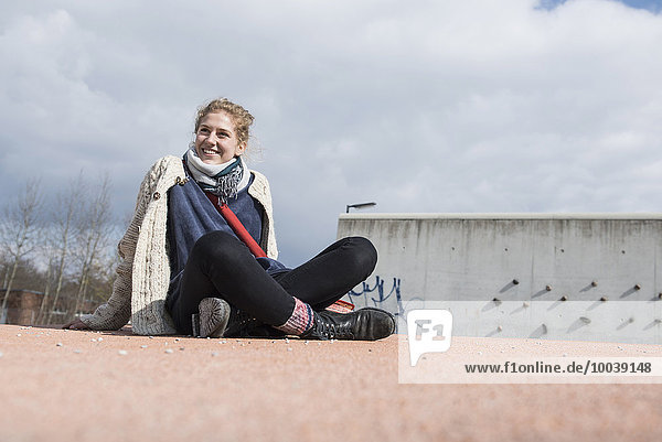 Young woman sitting cross-legged on playground turntable and smiling  Munich  Bavaria  Germany