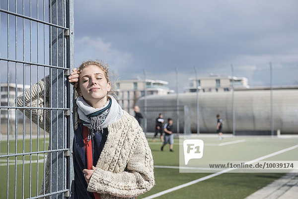 Young woman leaning on metal fence with eyes closed  Munich  Bavaria  Germany