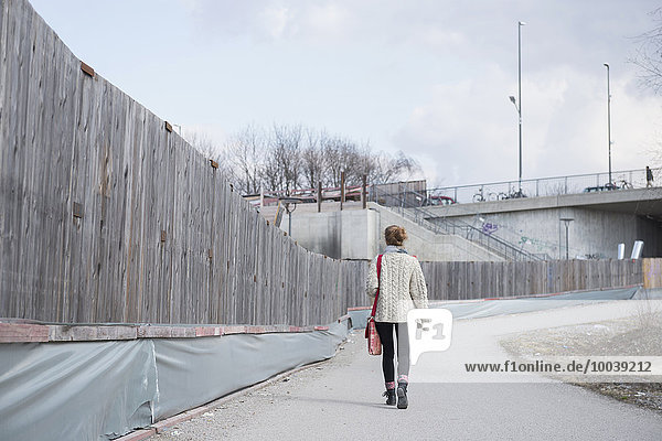 Rear view of a young woman walking along construction site fence on road  Munich  Bavaria  Germany