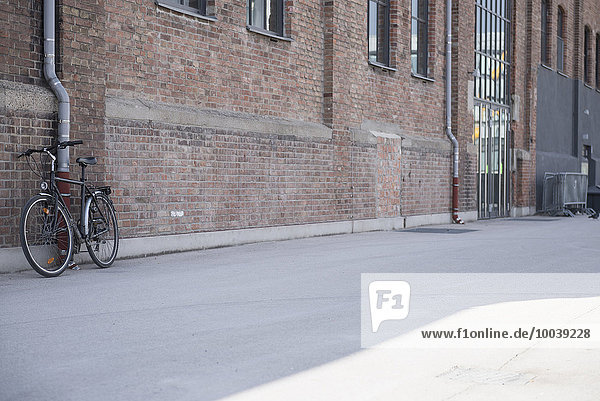 Bicycle leaning against a wall made of brick  Munich  Bavaria  Germany