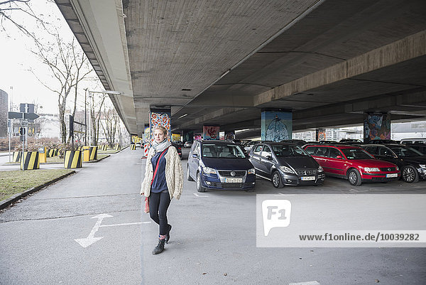 Young woman in a parking lot under a bridge made of concrete  Munich  Bavaria  Germany