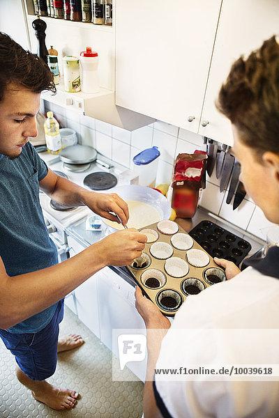 Young men making cupcakes