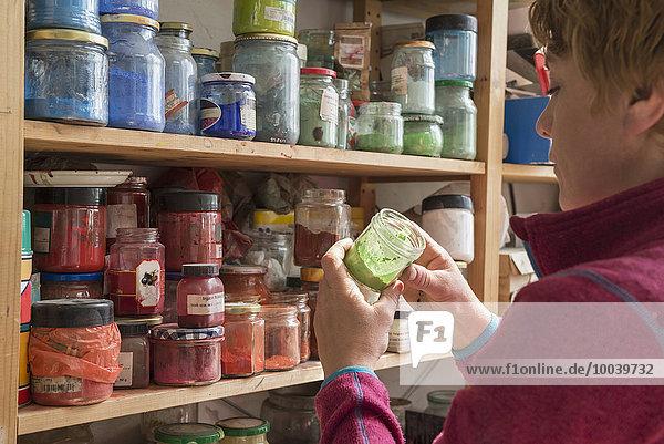 Female painter holding color bottle in art studio  Bavaria  Germany