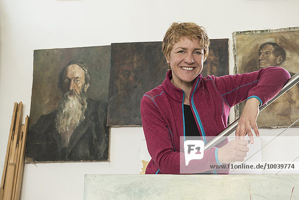 Portrait of a female artist smiling in her studio  Bavaria  Germany Portrait of a female artist smiling in her studio, Bavaria, Germany