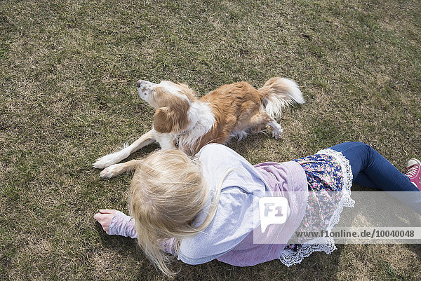 Teenage girl lying in park with her dog  Munich  Bavaria  Germany