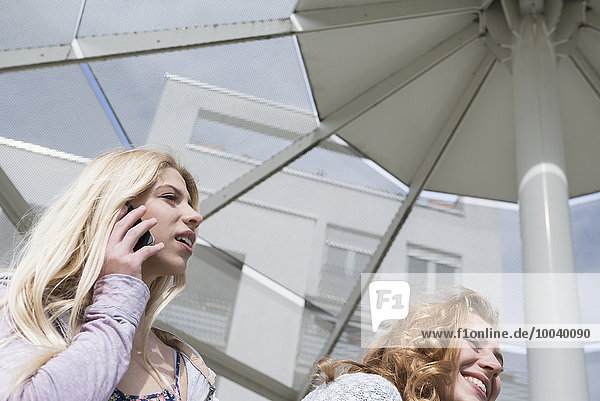 Teenage girl with her friend talking on mobile phone  Munich  Bavaria  Germany