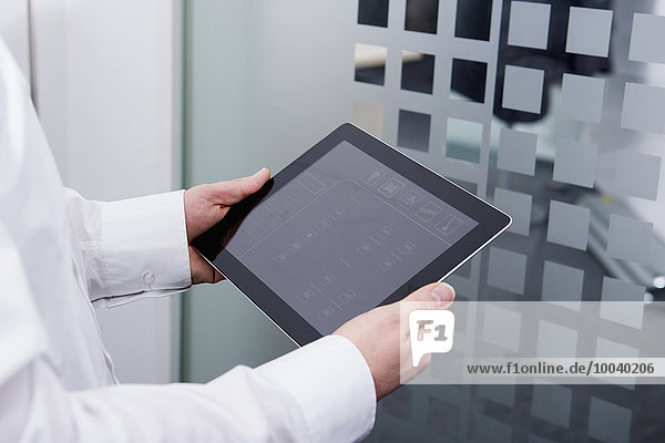 Man operating digital tablet in office  Munich  Bavaria  Germany