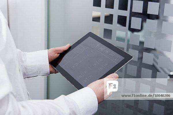 Man operating digital tablet in office  Munich  Bavaria  Germany