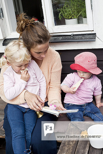 Mother reading book to daughters