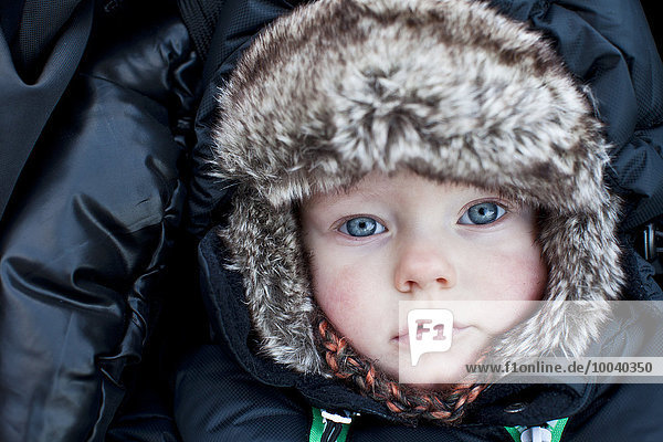 Portrait of baby boy wearing fur hat