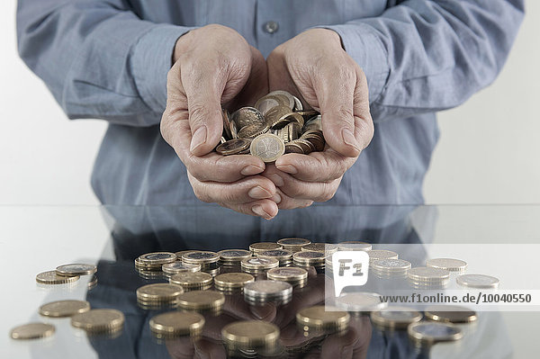 Businessman with handful of coins  Bavaria  Germany Businessman with handful of coins, Bavaria, Germany