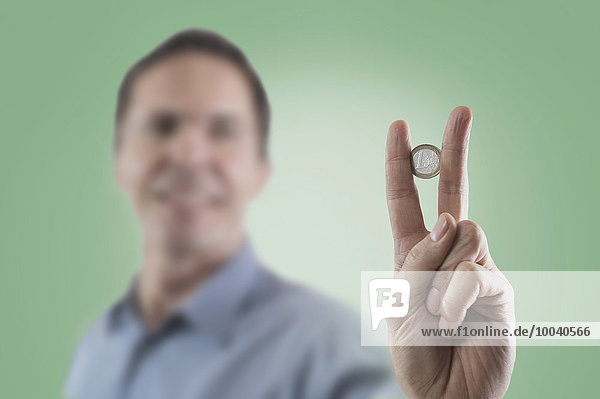 Businessman holding one euro coin between two fingers  Bavaria  Germany Businessman holding one euro coin between two fingers, Bavaria, Germany