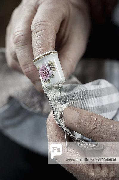 Senior female fashion designer wearing a thimble stitching in workshop  Bavaria  Germany