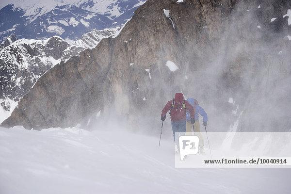 Ski mountaineers climbing on snowy mountain in snow storm  Zell Am See  Austria Ski mountaineers climbing on snowy mountain in snow storm, Zell Am See, Austria
