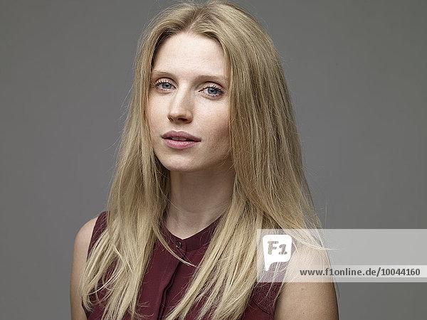 Porträt der träumenden blonden jungen Frau