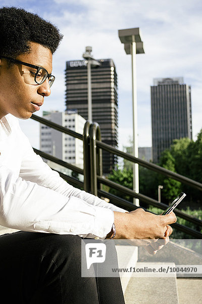 Young man sitting on stairs looking at cell phone