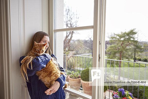 Teenagerin mit Katze durchs Fenster schauend