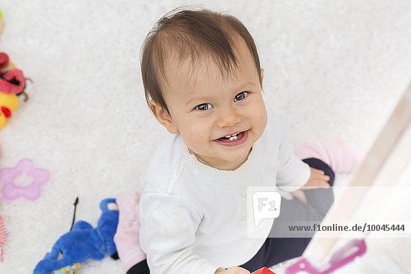 Lachendes kleines Mädchen auf dem Boden sitzend mit Spielzeug