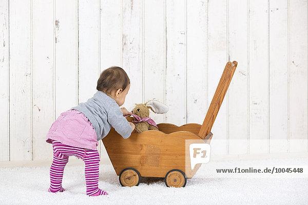 Kleines Mädchen spielt mit Plüschtier im Puppenwagen
