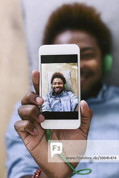 Junger Afroamerikaner  auf dem Boden liegend  mit Selbstmitleid