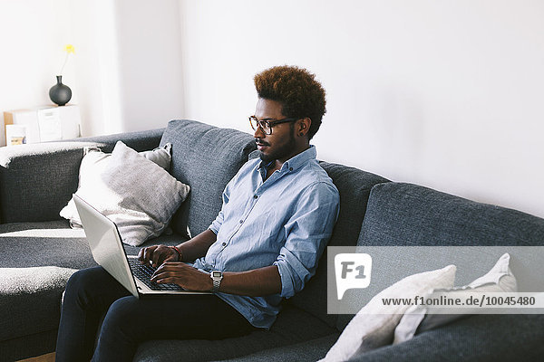 Young Afro American man sitting on couch  using laptop