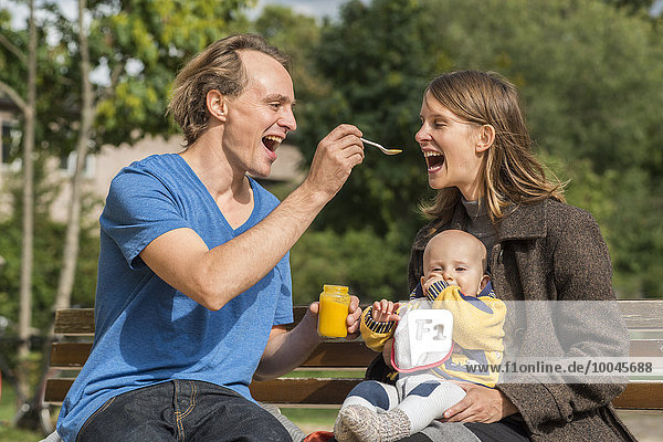 Happy family with baby food on bench