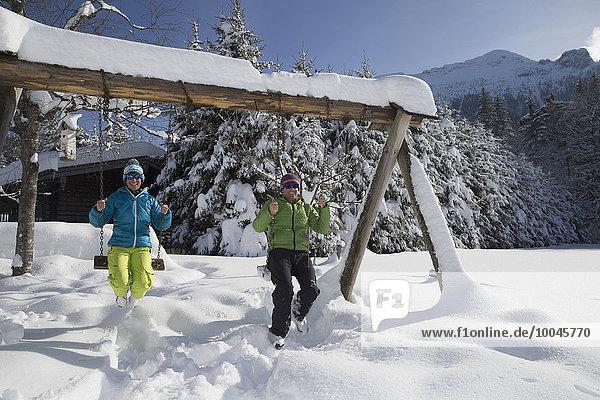 Deutschland  Bayern  Inzell  Paar sitzend auf Schaukeln in verschneiter Landschaft