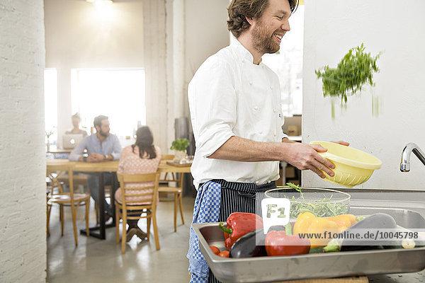 Koch eines kleinen Restaurants  das in der Küche Salat zubereitet.
