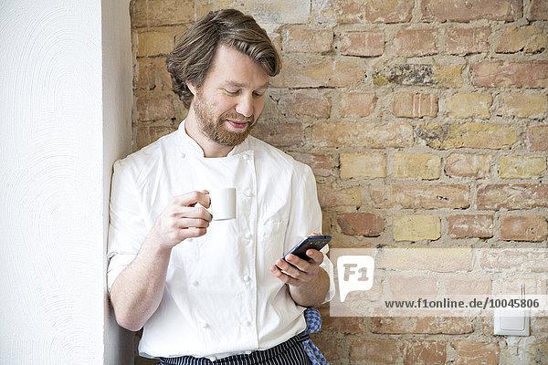 Koch mit Espressotasse und Smartphone zum Ausruhen
