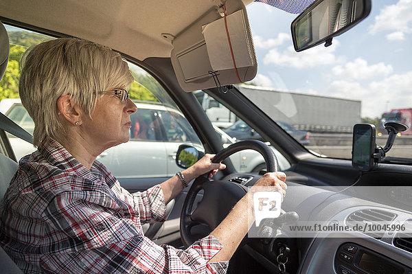 Deutschland  Brandenburg  Seniorin beim Autofahren auf der Autobahn