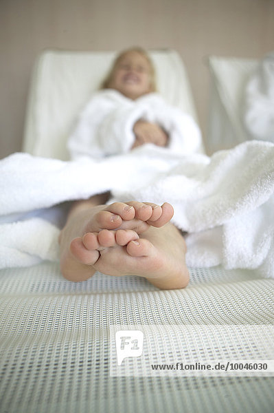Barefoot girl lying on couch at hotel spa