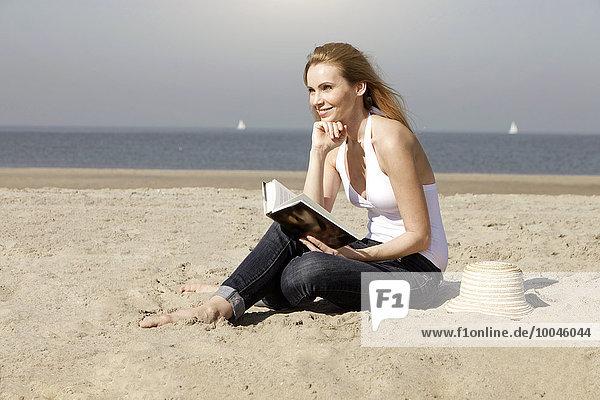Niederlande  Scheveningen  junge Frau mit Buch am Sandstrand sitzend