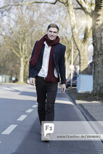 Portrait of smiling young man walking on street