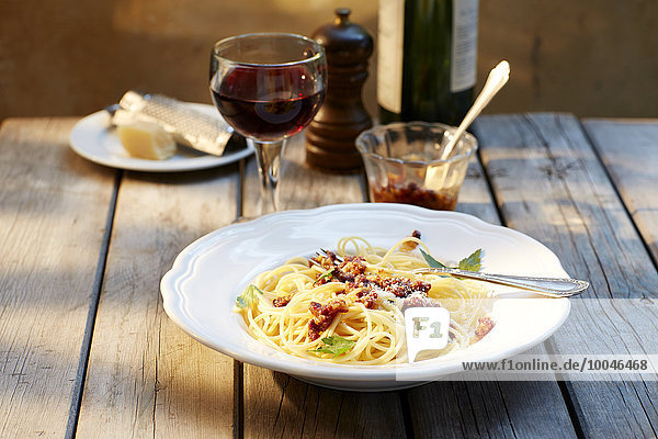 Spaghetti mit Tomatenpesto und geriebenem Parmesan und einem Glas Rotwein