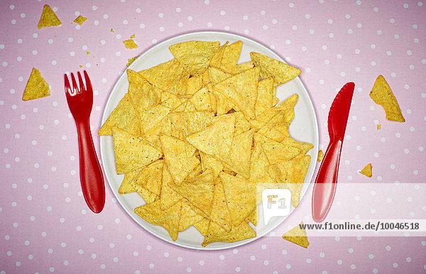 Teller mit Käse-Nachos und rotem Plastikbesteck auf rosa Tuch
